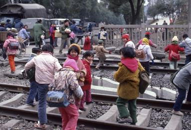 people crossing chinese steam trains lines in Guilin